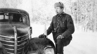 Pekka Tiilikainen seisoo piippu suussa auton vieressä talvimaisemassa.