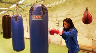 Nuori nainen hakkaa nyrkkeilysäkkiä.