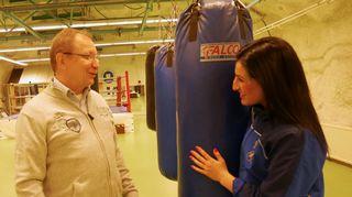 Mies ja nuori nainen keskustelevat nyrkkeilysalilla.