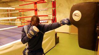 Mies iskee säkkiä nyrkkeilysalilla.