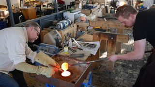 Kaksi miestä tekee hiekkavalulla lasikoriste-esinettä.