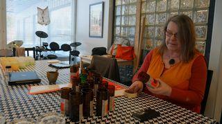 Nainen on pöydän ääressä lasien kanssa.