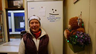 Nainen poseeraa jääkaapin edessä grillillä.