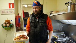 Mies esittelee grillillä makkaraperuna-annosta pekonilla.