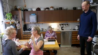 Ihmisiä keittiön pöydän äärellä Naruskan Retkeilymajalla.