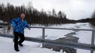 Mies poseeraa talvisen kosken äärellä silllalla.