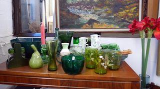 Vihreitä lasiesineitä pöydällä.
