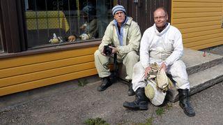 Kaksi miestä mehiläishoitopuvuissa talon rappusilla.