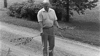 Kaivonkatsoja kulkee tietä varpu kädessä vesisuonta ja kaivon paikkaa etsien. Kuva on vuodelta 1986.