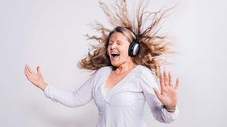 Kuuntelijan lista - nainen kuuntelee musiikkia kuulokkeilla, hiukset nousevat ihastuksesta pystyyn