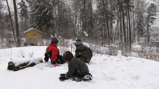 Lapset leikkivät lumessa metsässä kaupungissa.