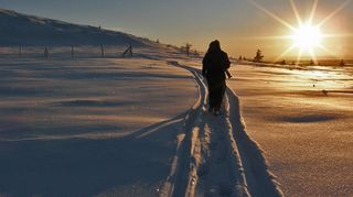 Vaeltaja talvisessa maisemassa, auringon paistaessa