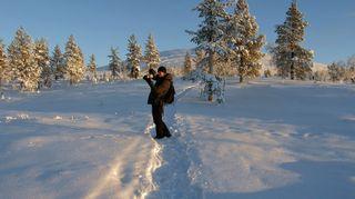 Lumisessa maisemassa retkeilijä ottaa valokuvaa
