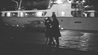 Poliisi saattaa laivatyttöä satamalaiturilla huoltopolisiin satamaan tekemässä ratsiassa 1.1.1960.