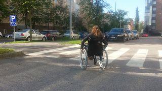 Kuvassa toimittaja kelaa pyörätuolilla kadulla.