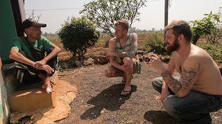 Kolme miestä  juttelee talon pihassa.
