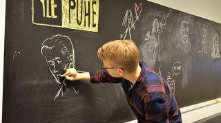 Kuvassa Teppo Säkkinen piirtää poliittista omakuvaa.