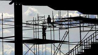 Kuvassa miehet rakennustelineillä.