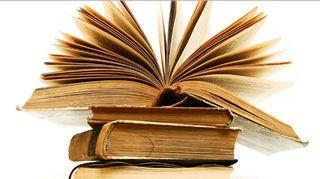 Kuvassa vanhoja kirjoja pinossa.