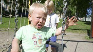 Kuvassa lapsi itkee keinussa.