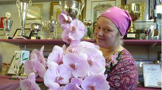 Floristimestari Pirjo Koppi kädessään kukkia, taustalla pokaaleja.