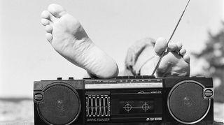Kuvassa mies kuuntelee rannalla radiota.