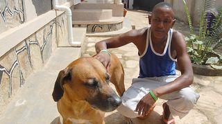 Kuvassa mies ja koira Ugandassa.