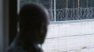 Kuvassa vanki katsoo sisältä sisäpihalle, jossa näkyy piikkilanka-aita.
