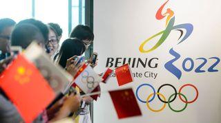 Kuvassa kiinalaisia Pekingin olympialaiskyltin edessä.
