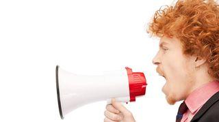Kuvassa mies huutaa megafoniin.