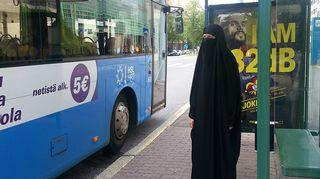 Kuvassa toimittaja Salla Vuolteenaho niqabi päällä bussipysäkillä.