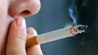 Kuvassa nainen polttaa tupakkaa.