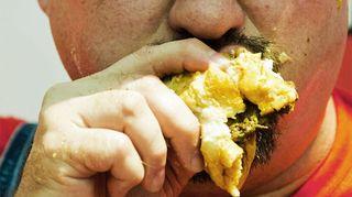 Kuvassa mies ahmii hampurilaista.
