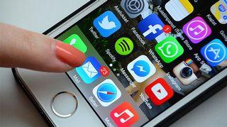 Kuvassa nainen käyttää sähköpostia älypuhelimen kautta.