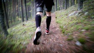 Kuvassa mies juoksee metsässä.