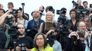 Valokuvaajia kameroinen muotinäytöksessä.