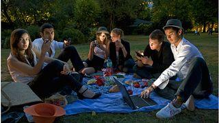 Kuvassa nuoret ovat piknikillä ja tutkivat älylaitteitaan.