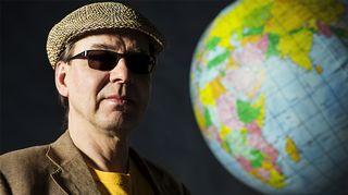 Harri Tuominen ja maapallo. Kuva: Yle.