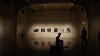 Mies istuu taidenäyttelyssä