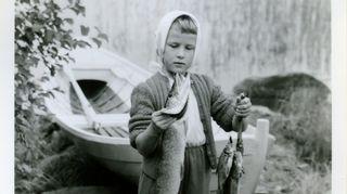 Päivi Kärkkäinen lapsena huivi päässä venerannassa kalansaalis käsissä