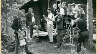 Kuvaus- ja äänoitystilanne kesämökin pihalla, lapsiryhmä ja miehiä Tv-nauhoitusta tekemässä