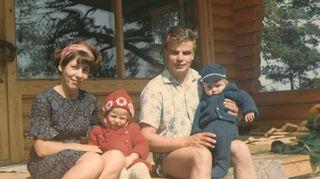 Petri, sisko ja vanhemmat mökin terassilla.