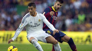 Real Madridin Cristiano Ronaldo (vas.) pitää palloa. Barcelonan Gerard Piqué (oik.) seuraa.