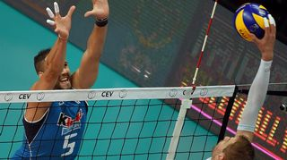 Italy's Osmany Juantorena Portuondo (L) tries to block the smash by Finland's Olli-Pekka Ojansivu