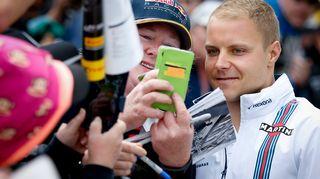 Valtteri Bottas asettuu kuvan fanin kanssa.