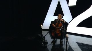 Osmo Ikonen soittaa selloa suuren A2-kyltin edessä.