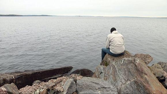 Yksinäinen mies järven rannassa.