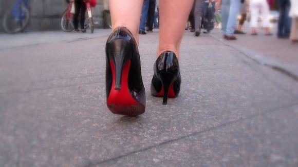 Nainen kävelee kadulla korkokengät jalassa.