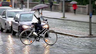 Pyöräilijä ylittää kadun sateessa