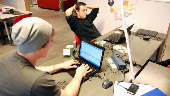 Kaksi miestä katselee kannettavien tietokoneiden näyttöjä.